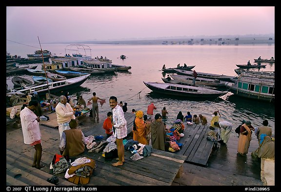 Men preparing for ritual bath on banks of Ganges River at dawn. Varanasi, Uttar Pradesh, India
