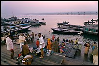 Men preparing for ritual bath on banks of Ganges River at dawn. Varanasi, Uttar Pradesh, India (color)