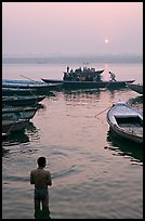 Man standing in Ganga River and boats at sunrise. Varanasi, Uttar Pradesh, India