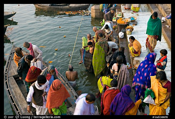 Hindu pilgrims walk out of boat onto Dasaswamedh Ghat. Varanasi, Uttar Pradesh, India (color)