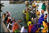 Hindu pilgrims walk out of boat onto Dasaswamedh Ghat. Varanasi, Uttar Pradesh, India ( color)