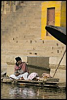 Man sitting near unbrella. Varanasi, Uttar Pradesh, India ( color)