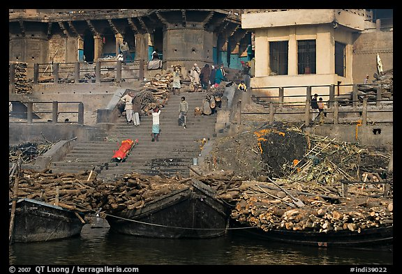 Steps of Manikarnika Ghat with body swathed in cloth and firewood piles. Varanasi, Uttar Pradesh, India