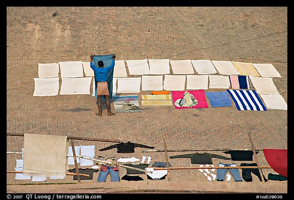 Man laying out laundry for drying. Varanasi, Uttar Pradesh, India