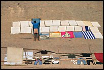 Man laying out laundry for drying. Varanasi, Uttar Pradesh, India (color)