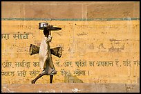 Man carrying a plater in front of wall with inscriptions in Hindi. Varanasi, Uttar Pradesh, India ( color)