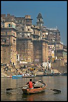 Man rowing boat beneath Munshi Ghat. Varanasi, Uttar Pradesh, India