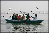 Indian tourists on rawboat surrounded by birds. Varanasi, Uttar Pradesh, India