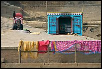 Sadhu sitting next to shrine and laundry. Varanasi, Uttar Pradesh, India ( color)