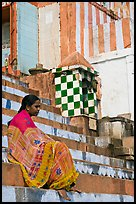 Woman sitting on temple steps. Varanasi, Uttar Pradesh, India