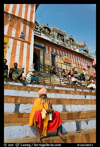 Holy man sitting on temple steps, Kedar Ghat. Varanasi, Uttar Pradesh, India