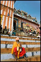 Holy man sitting on temple steps, Kedar Ghat. Varanasi, Uttar Pradesh, India (color)