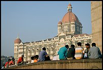 Men sitting in front of Taj Mahal Palace Hotel. Mumbai, Maharashtra, India (color)
