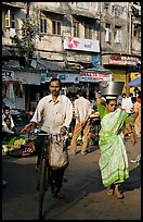 Man riding bike and woman with basket on head, Colaba Market. Mumbai, Maharashtra, India ( color)