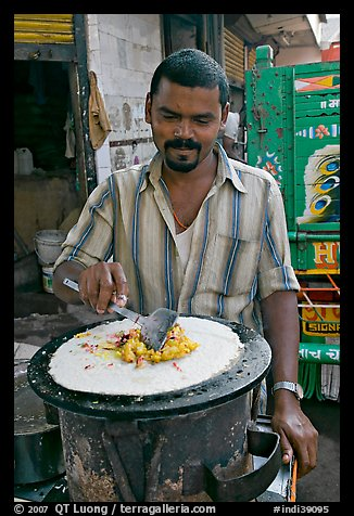 Man preparing breakfast dosa, Colaba Market. Mumbai, Maharashtra, India (color)