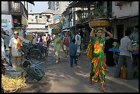 Women carrying  baskets on head in narrow street, Colaba Market. Mumbai, Maharashtra, India