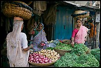 Women with baskets on head buying vegetables, Colaba Market. Mumbai, Maharashtra, India