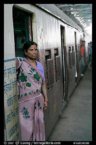 Woman standing at door of suburban train. Mumbai, Maharashtra, India (color)