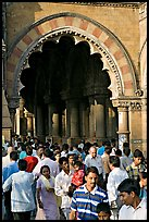 Crowd pass beneath an archway, Chhatrapati Shivaji Terminus. Mumbai, Maharashtra, India (color)