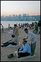 Head masseurs and Mumbai skyline at sunset,  Chowpatty Beach. Mumbai, Maharashtra, India