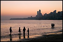 People standing in water at sunset with skyline behind, Chowpatty Beach. Mumbai, Maharashtra, India (color)