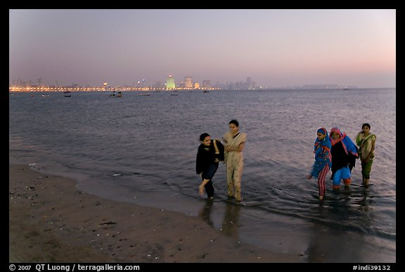 Women walking in water by night, Chowpatty Beach. Mumbai, Maharashtra, India
