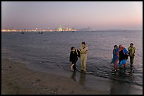 Women walking in water by night, Chowpatty Beach. Mumbai, Maharashtra, India (color)