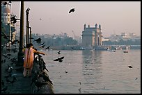 Woman feeding birds, with Gateway of India in background, early morning. Mumbai, Maharashtra, India (color)
