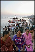 Women sitting on waterfront with boats behind at twilight. Mumbai, Maharashtra, India