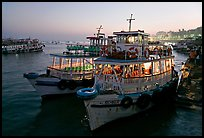 Lighted tour boat at quay,  sunset. Mumbai, Maharashtra, India (color)