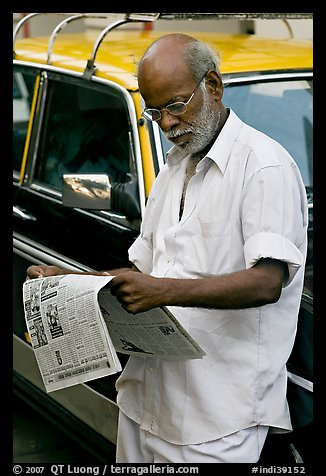 Man reading newspaper next to taxi. Mumbai, Maharashtra, India