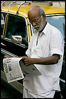 Man reading newspaper next to taxi. Mumbai, Maharashtra, India (color)