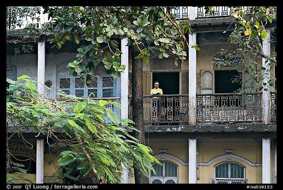 Facade with balconies and man reading. Mumbai, Maharashtra, India (color)