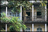 Facade with balconies and man reading. Mumbai, Maharashtra, India