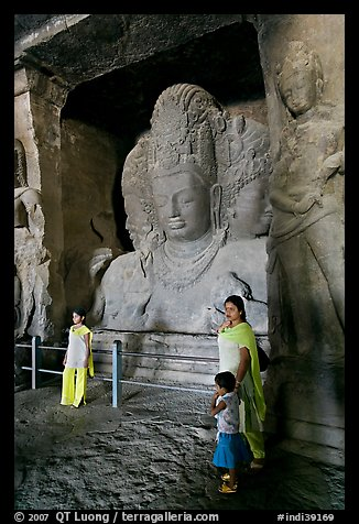 Woman and children standing in front of Mahesh Murti, main  Elephanta cave. Mumbai, Maharashtra, India