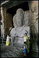Woman and children standing in front of Mahesh Murti, main  Elephanta cave. Mumbai, Maharashtra, India (color)