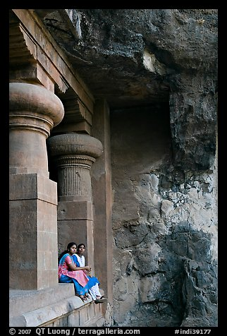 Women sitting at entrance of cave, Elephanta Island. Mumbai, Maharashtra, India