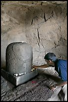 Man venerating a Linga in Shiva shrine, Elephanta Island. Mumbai, Maharashtra, India
