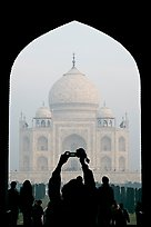Visitor pointing  digital camera to Maj Mahal, framed by arch of gateway. Agra, Uttar Pradesh, India