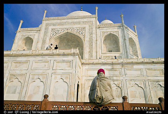 Woman sitting at the base of Taj Mahal looking up. Agra, Uttar Pradesh, India