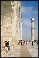 Couple sitting on side pishtaq and visitors strolling on platform, Taj Mahal. Agra, Uttar Pradesh, India