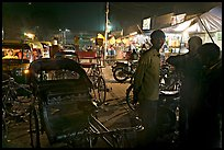 Cycle-rickshaws and vending booths at night, Agra cantonment. Agra, Uttar Pradesh, India (color)