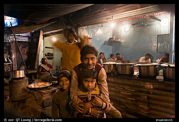 Children and food booth at night, Agra cantonment. Agra, Uttar Pradesh, India (color)