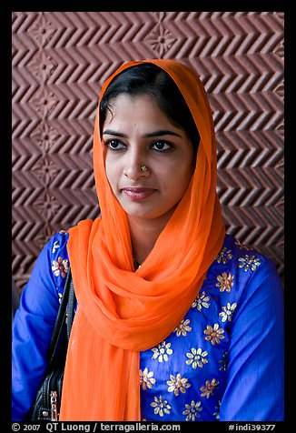 Young woman with bright scarf, in front of Rumi Sultana motifs. Fatehpur Sikri, Uttar Pradesh, India