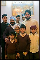 Sikh men and boys in front of picture of the Golden Temple. Bharatpur, Rajasthan, India