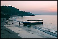 Narrow boat on beach at dawn, Dona Paula. Goa, India