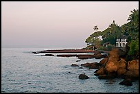 Boulders, beachfront house, and palm trees at sunrise. Goa, India