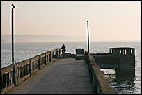 Pier with man fishing, early morning, Dona Paula. Goa, India