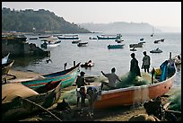 Men repairing net in small fishing boat, early morning, Dona Paula. Goa, India (color)