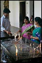 Man and two women burning candles, Basilica of Bom Jesus, Old Goa. Goa, India (color)